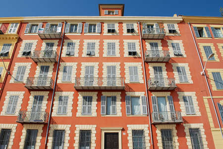 stucco house: Nice, France - July 21, 2009: Exterior of the beautiful red stucco house with traditional french shutter windows and balconies in Nice, France.