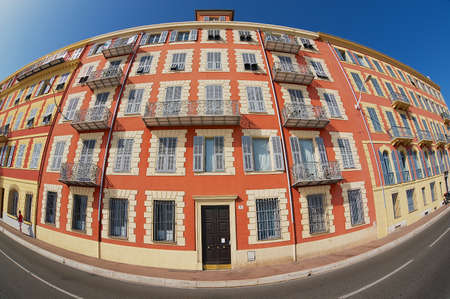 stucco house: Nice, France - July 21, 2009: Exterior of the beautiful red stucco house with traditional french shutter windows and balconies in Nice, France. Filmed with a wide angle lens.