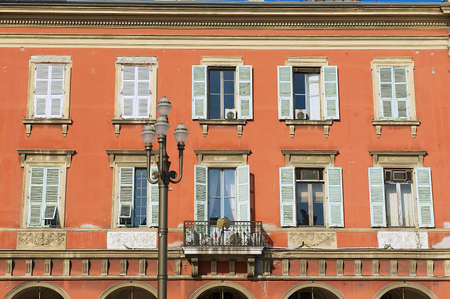 stucco house: Nice, France - July 21, 2009: Exterior of the beautiful red stucco house with traditional french shutter windows in Nice, France.