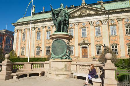 nobility: Stockholm, Sweden, April 04, 2011 - Lady relaxes at the bench in front of the House of Nobility and statue of Gustaf Eriksson Vasa in Stockholm, Sweden.