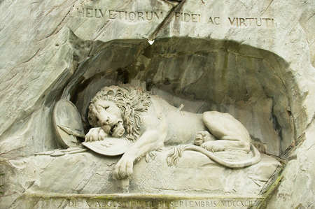 sculptures: Lucerne, Switzerland - February 19, 2012: View to the Dying Lion monument in Lucerne, Switzerland. Carved in the rock to honor the Swiss Guards of Lois XVI of France.