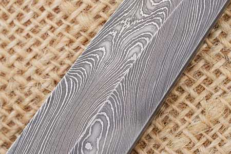 Fragment of the traditional handmade Finnish knife blade with the abstract wave pattern of damascus steel over an old sack background. Reklamní fotografie - 51041739