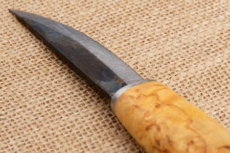 finnish: Traditional rough handmade Finnish knife with the wooden birch handle over an old sack background.