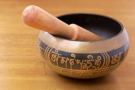 gong bowl: Singing bowl with wooden stick on the golden painted metal surface. Singing bowl is a typical and popular souvenir from Nepal. Stock Photo