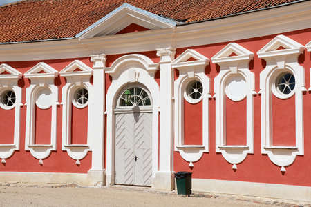 rundale: Pilsrundale, Latvia - July 27, 2015: Exterior of the red painted stables building windows next to Rundale palace in Pilsrundale, Latvia.
