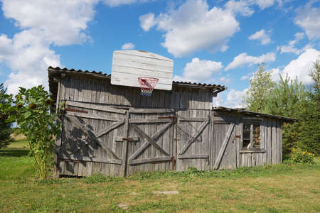 Old wooden barn with a basketball hoop attached.