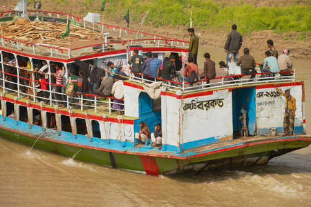 Chhota Dhulandi, Bangladesh, February 19, 2014 - People cross Padma river on Daulatdia ferry boat at Chhota Dhulandi, Bangladesh. Passenger ferry boats are often overloaded in Bangladesh.