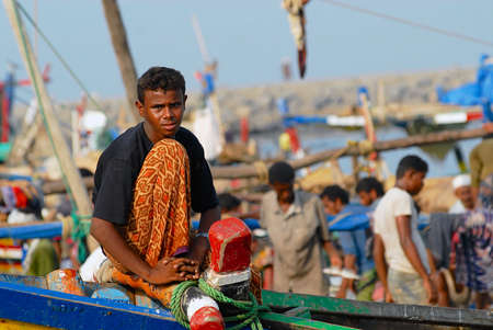 Al Hudaydah, Yemen, September 17, 2006 - Fisherman sits at the front side of the fishing boat just arrived to the port in Al Hudaydah, Yemen.