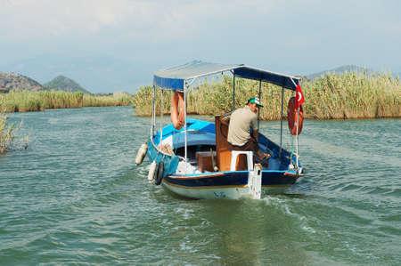 cruising: Mugla, Turkey, August 13, 2009 - Man rides tourist boat at the Dalyan river in Mugla, Turkey.