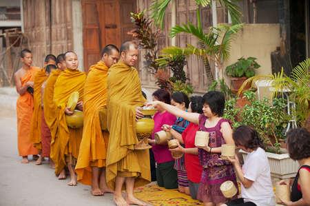 Chiang Khan, Thailand, 18 april 2010 - Mensen bieden kleefrijst aan boeddhistische monniken in de ochtend in Chiang Khan, Thailand.
