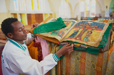 Aksum, Ethiopia, January 25, 2010 - Man demonstrates the ancient Bible in the Amharic language in the church of Our Lady of Zion, the most sacred place for all the Eastern Ethiopians in Aksum, Ethiopia.