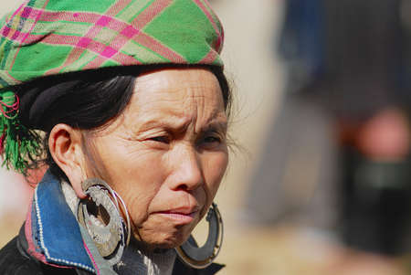 Sapa, Vietnam - February 10, 2007: Portrait of a Black Miao (Hmong) woman with a traditional costume with silver earrings at the street in Sapa, Vietnam.