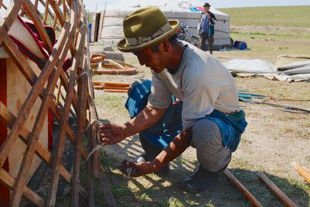 Karkhorin, Mongolei, 25. August 2006 - Der mongolische Mann baut den Holzrahmen einer Jurte (ger oder Nomadenzelt) in der Steppe in Kharkhorin, Mongolei zusammen.