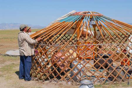 Kharkhorin, Mongolei, 25. August 2006 - Mongolische Männer bauen Jurte (Nomadenzelt) in der Steppe in Kharkhorin, Mongolei zusammen. Der hölzerne Rahmen einer Jurte ist mit Filzstücken bedeckt.