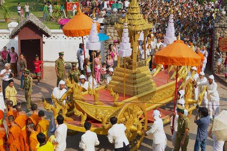 LUANG PRABANG, LAOS - APRIL 16, 2012: Mensen nemen deel aan de religieuze processie nadat Pra Bang (de belangrijkste Buddah van Luang Prabang) uit het Koninklijk Paleis naar de Wat Mai-boeddhistische tempel is gehaald tijdens Phi Mai (Lao Nieuwjaar) vieringen in Luang Pra