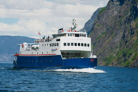 FLAM, NORWAY - JUNE 08,2012: Ferry boat arrives to the port at the Aurlandsfjord in Flam, Norway. Standard-Bild - 110868785