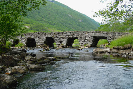 Summer landscape with an old stone bridge across the small river in rural Norway. Фото со стока