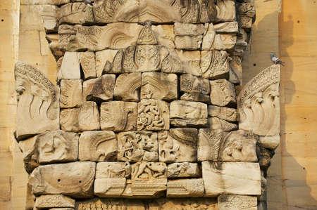 Scultura in pietra arenaria con motivi religiosi presso le rovine del tempio indù nel parco storico di Phimai (Prasat Hin Phimai) in Thailandia.