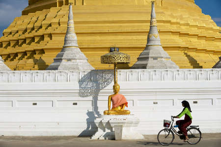 Mae Sot, Thailand - November 20, 2013: Woman rides bicycle in front of the Wat Chumphon Khiri Buddhist stupa in Mae Sot, Tak province, Thailand. This stupa is a copy of the Shwedagon Pagoda in Myanmar. 報道画像
