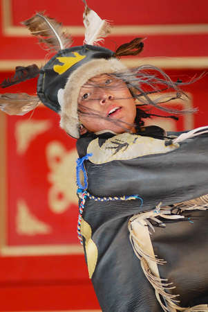 Ulaanbaatar, Mongolia - August 16, 2006: Young man wearing shamans costume performs traditional ceremony in Ulaanbaatar, Mongolia.