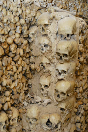 Sives, Portugal - July 18, 2006: Human skulls and bones fixed in the wall of the Chapel of Bones (Capella dos Ossos) at Alcantarilha in Silves, Portugal.
