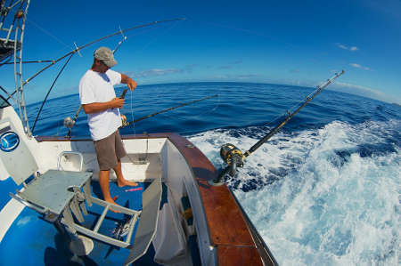 Saint-Denis, Réunion - 8 décembre 2010 : Un marin non identifié prépare des moulinets et des cannes pour la pêche au marlin en mer près de Saint-Denis, île de la Réunion.