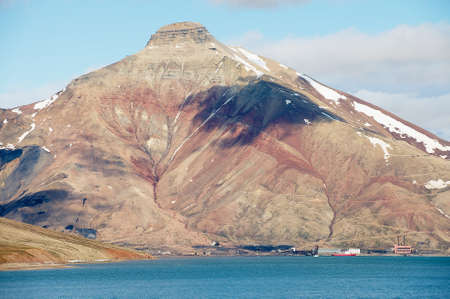 View to the abandoned Russian arctic settlement Pyramiden with the natural mountain in the form of pyramid above, Norway.