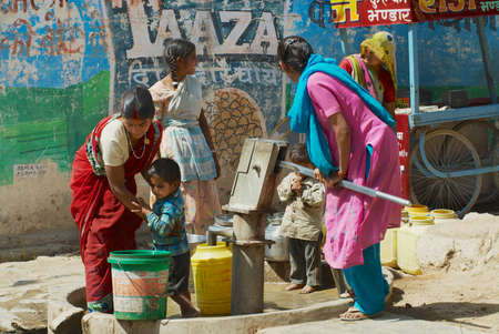 Orchha, India - March 27, 2007: Unidentified women with kids pump water to plastic containers with a hand pump at the street in Orchha, India.