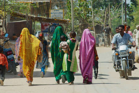 Orchha, India - March 27, 2007: Unidentified Indian women wearing colorful sarees walk by the street in Orchha, India. Editorial