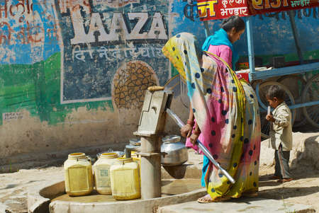 Orchha, India - March 27, 2007: Unidentified woman pumps water to plastic containers with a hand pump at the street in Orchha, India.