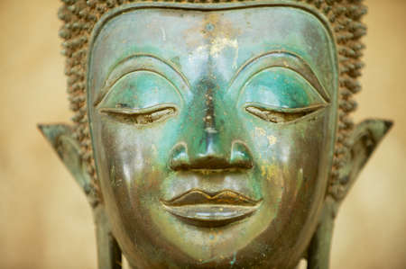 Close up of a face of an ancient copper Buddha statue outside of the Hor Phra Keo temple (former temple of the Emerald Buddha) in Vientiane, Laos. Banco de Imagens
