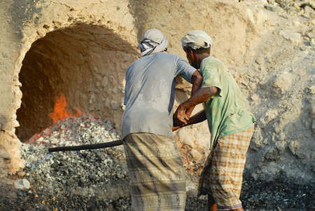 Aden, Yemen - September 14, 2006: Unidentified men wearing traditional head scarfs and squirts work at an outdoor coal production oven in Aden, Yemen. Editorial