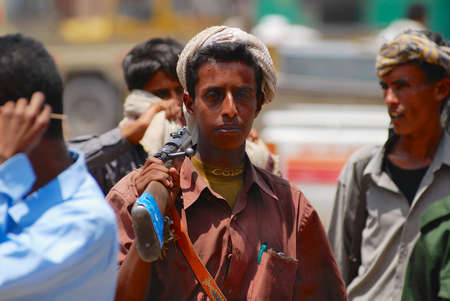 Aden, Yemen - September 14, 2006: Unidentified young Yemeni man holds a rifle at the street in Aden, Yemen. Editorial