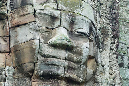 Stone carved face at the wall of the Bayon temple in Siem Reap, Cambodia. Imagens