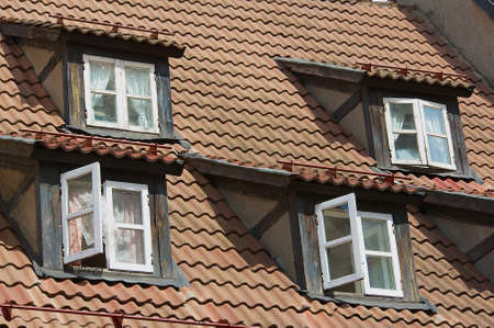 Vintage windows at the attic roof with brown tiles in the historical part of Riga, Latvia.