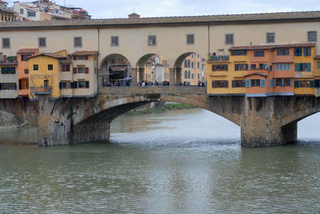 Florence, Italy - March 01, 2007: People pass by the Ponte Vecchio bridge over Arno river in Florence, Italy.