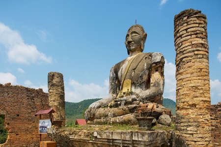Phonsavan, Laos - April 19, 2012: Ruin of the Wat Phia Wat temple with damaged Buddha statue in Phonsavan, Laos. This Buddha image in Phonsavan area survived US carpet bombings of Laos.