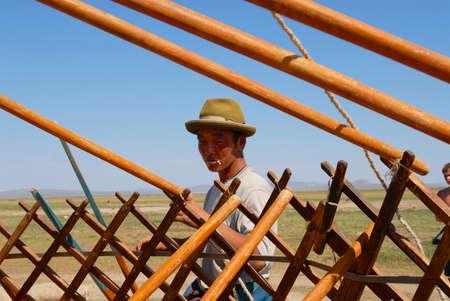 Karkhorin, Mongolei - 25. August 2006: Nicht identifizierter mongolischer Mann baut Holzrahmen einer Jurte (ger oder nomadisches Zelt) in der Steppe in Kharkhorin, Mongolei zusammen.