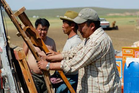 Karkhorin, Mongolei - 25. August 2006: Mongolische Männer montieren Holzrahmen einer Jurte (Ger oder Nomadenzelt) in der Steppe in Kharkhorin, Mongolei.