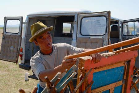 Karkhorin, Mongolia - August 25, 2006: Mongolian man assembles wooden frame of a yurt (ger or nomadic tent) in steppe in Kharkhorin, Mongolia. Editorial