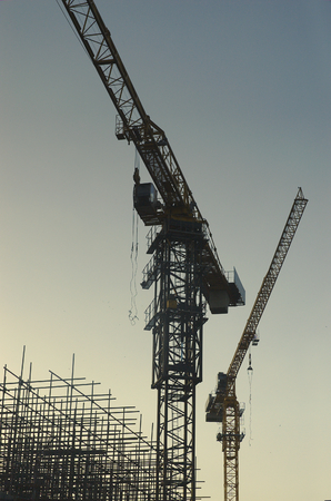 Two construction cranes and metal scaffolding silhouetted against the sky