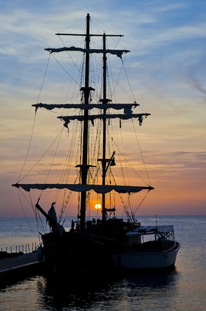 retro styled imagery: Pirate Ship at Sunset Stock Photo