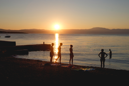 people silhouette on the beach at sunset in summer time Malinska, Isle of Krk Croatia
