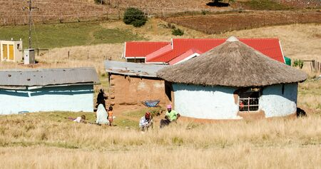 South african family near a traditional mud house in small village, South Africa, apartheid, zululand KwaZulu Natal