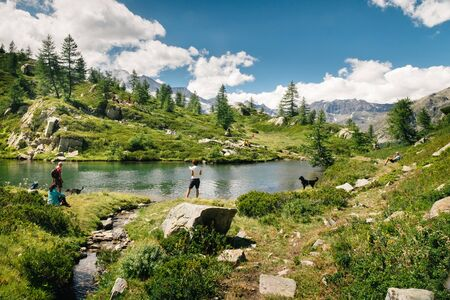 Mountain lake landscape with people near Bellagarda lake. Sense of freedom. Gran Paradiso National Park, Ceresole Reale, Piedmont, Italy Stockfoto