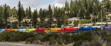 A line of trucks that are all of a different color. Banco de Imagens