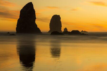The Needles at Cannon Beach durante una puesta de sol. La exposición prolongada hace que la ola se empañe. Foto de archivo - 87938143