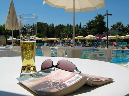 beer, book and sunglasses by the poolside