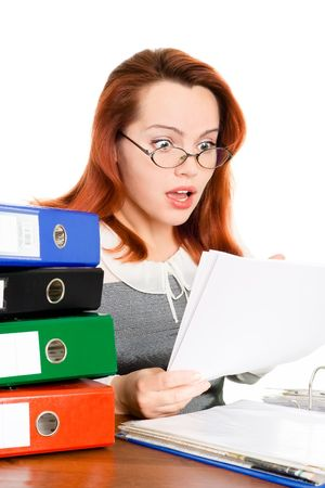 reckon: surprised business woman in glasses looking at the paper sitting at a table isolated on white