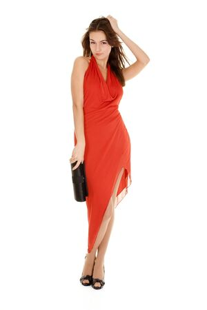 a charming young woman in a red evening gown flirting isolated on white Stock Photo